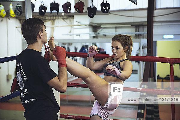 Kampfsportlerin im Sparring mit Trainer