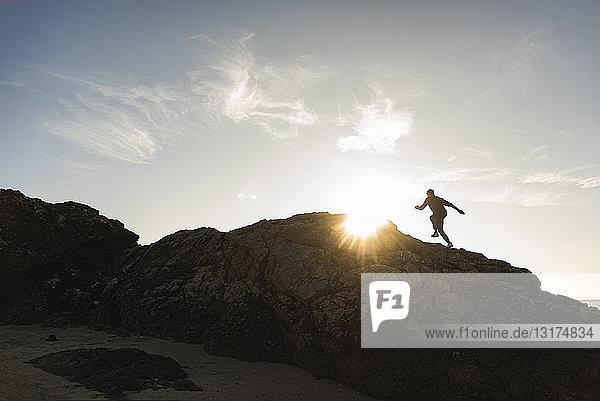 Frankreich  Bretagne  junger Mann rennt bei Sonnenuntergang auf einem Felsen