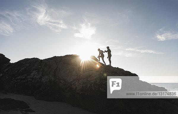 Frankreich  Bretagne  junges Paar klettert bei Sonnenuntergang auf einen Felsen am Strand
