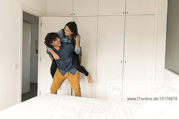 Fröhlicher Mann trägt Freundin huckepack im Schlafzimmer zu Hause