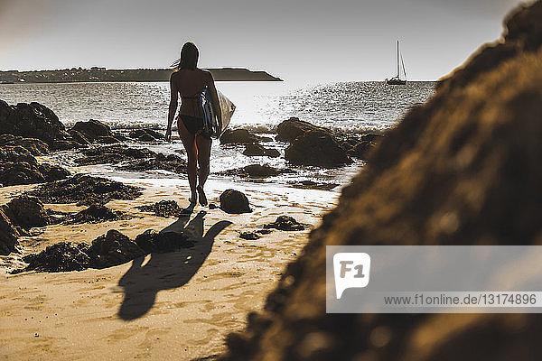 Frankreich,  Bretagne,  junge Frau trägt Surfbrett an einem felsigen Strand am Meer