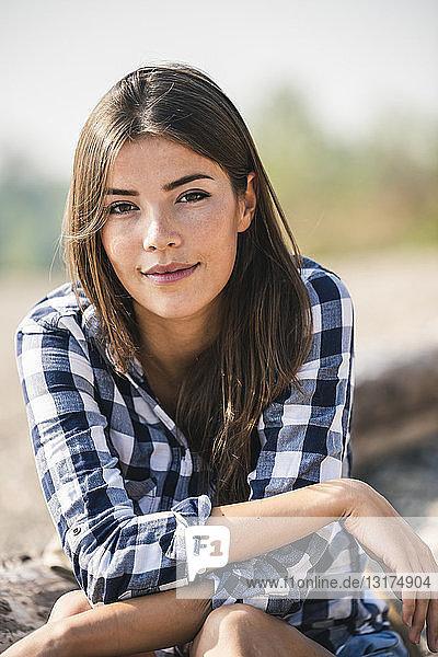 Porträt einer lächelnden jungen Frau  die im Freien sitzt