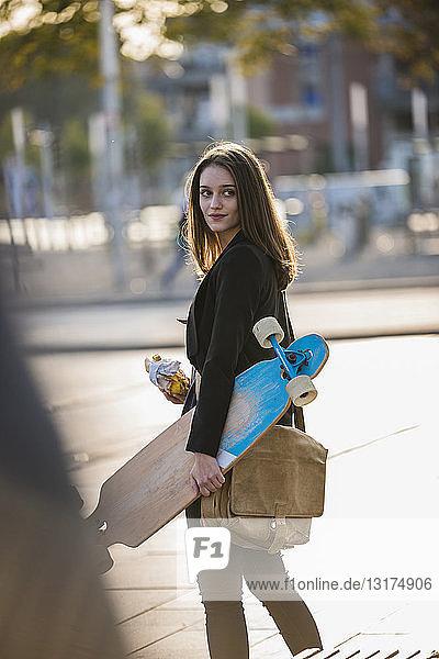 Junge Frau mit Longboard in der Stadt in Bewegung