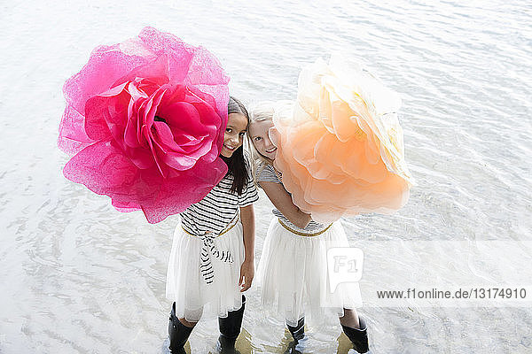 Two girls standing in a lake with two oversized artificial flowers