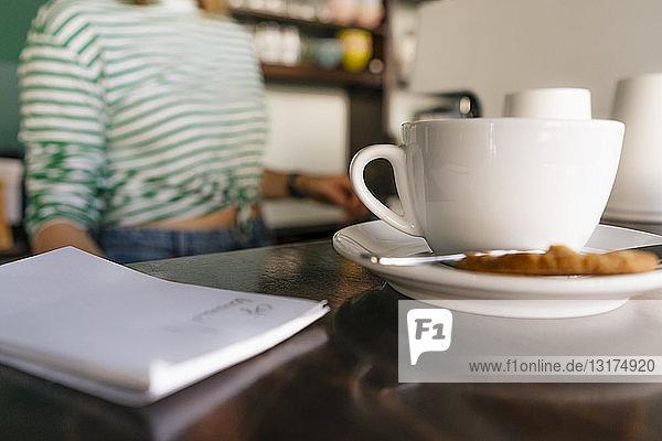 Tasse Kaffee und Notizblock auf Tisch in einem Café mit Frau im Hintergrund