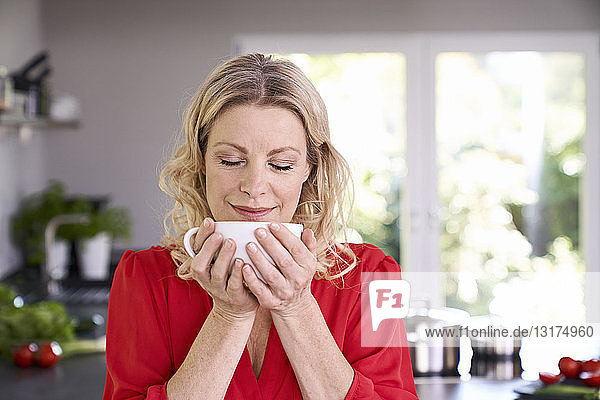 Portrait of woman enjoying cup of coffee in kitchen