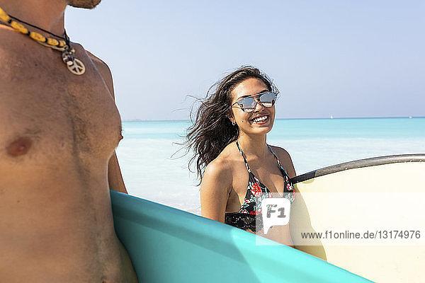 Junges Paar am Strand  Surfbretter tragend  Frau lächelnd