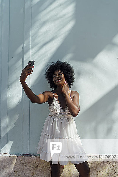 Smiling young woman wearing white dress taking a selfie at a wall