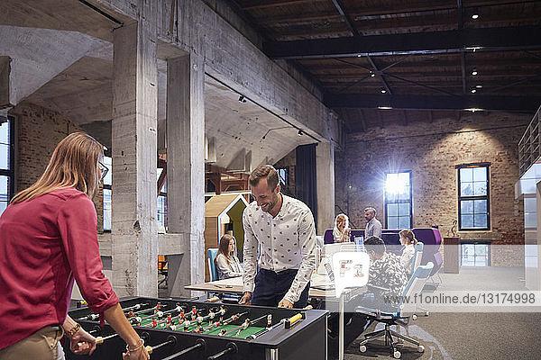 Business people in office taking a break  playing foosball