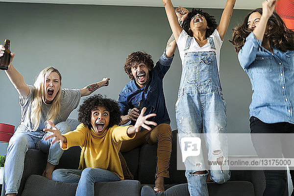Excited fans watching tv and cheering