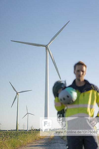 Unscharfe Sicht eines Technikers  der mit Kletterausrüstung auf einem Feldweg an einem Windpark steht