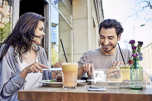 Glückliches junges Paar beim Mittagessen in einem Restaurant im Freien