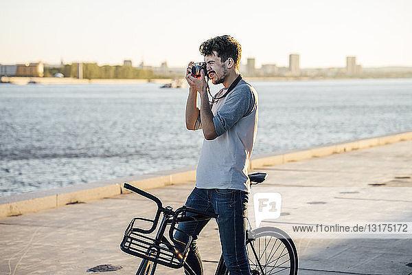 Junger Mann mit Pendler-Fixie-Fahrrad beim Fotografieren am Flussufer