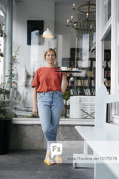 Porträt einer jungen Frau  die in einem Café Kaffee und Kuchen serviert