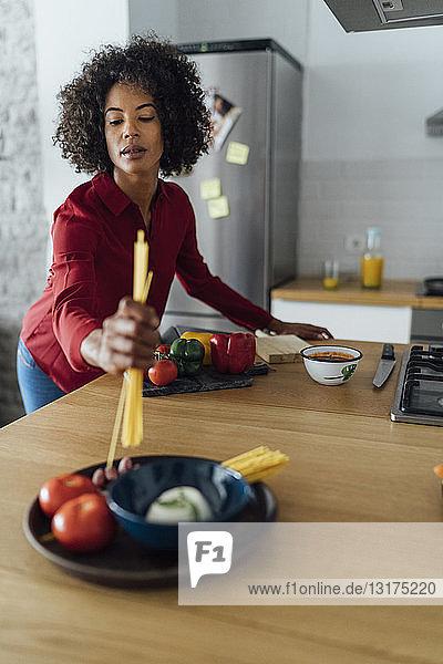 Woman standing in kitchen  preparing spaghetti