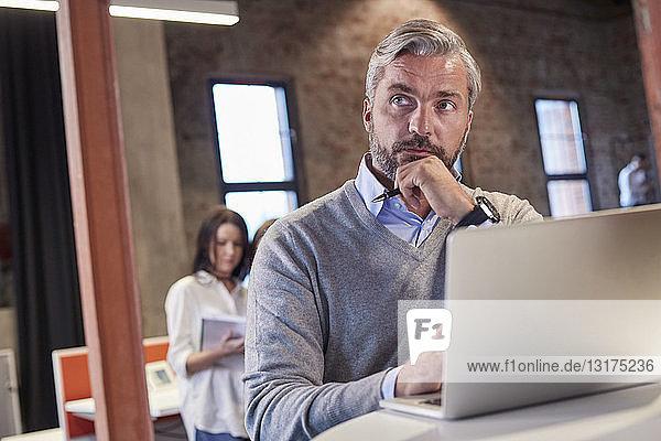 Mature man sitting at laptop  thinking