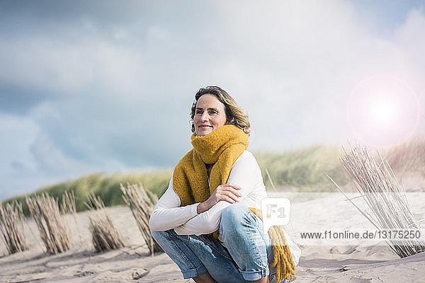 Reife Frau kauert in den Dünen und genießt den Wind