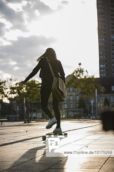 Rückansicht einer jungen Frau  die in der Stadt Longboard fährt