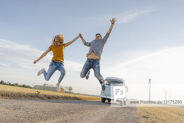 Überschwängliches Paar springt auf Feldweg am Wohnmobil in ländlicher Landschaft