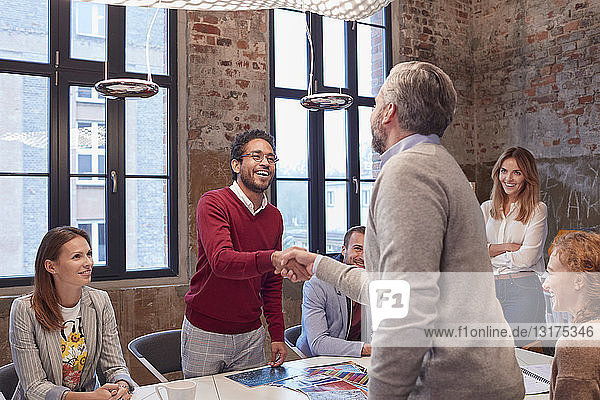 Colleagues greeting at a presentation in the office