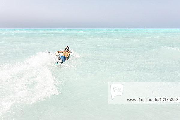 Junger Surfer paddelt  auf seinem Surfbrett liegend