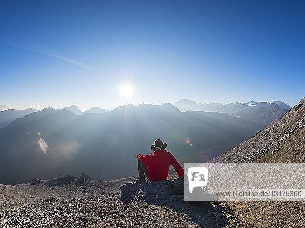 Grenzregion Italien Schweiz  älterer Mann macht Pause vom Wandern in der Berglandschaft am Piz Umbrail