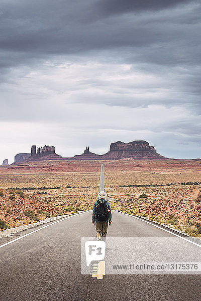 USA  Utah  Man with backpack walking on road to Monument Valley
