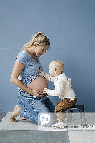 Kleinkind untersucht den Bauch der schwangeren Mutter