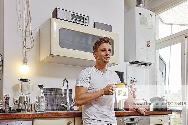 Smiling young man at home having a coffee break in kitchen