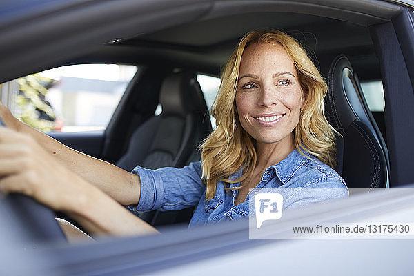 Lächelnde Auto fahrende Frau schaut aus dem Fenster