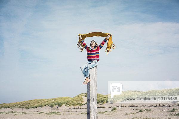 Reife Frau sitzt auf einem Holzpfahl am Strand und hält einen Schal im Wind