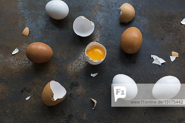 Ganze und geöffnete weiße und braune Eier auf rostigem Metall