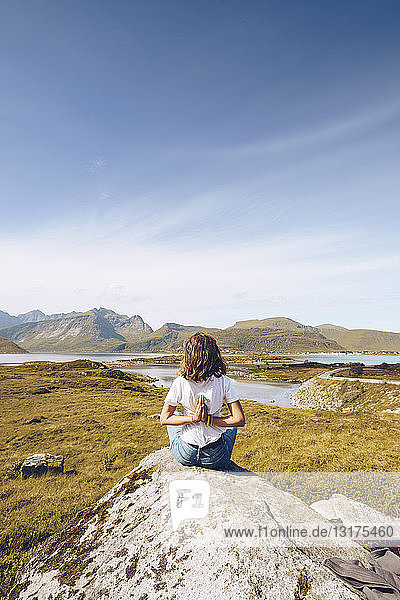 Norway  Lofoten  back view of young woman sitting on a rock doing yoga exercise