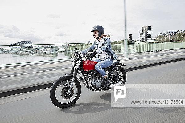 Deutschland  Köln  junge Frau mit Motorrad auf der Brücke