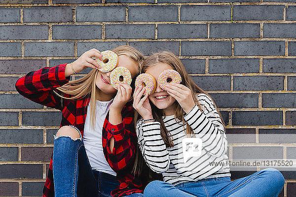 Zwei Mädchen amüsieren sich mit Doughnuts