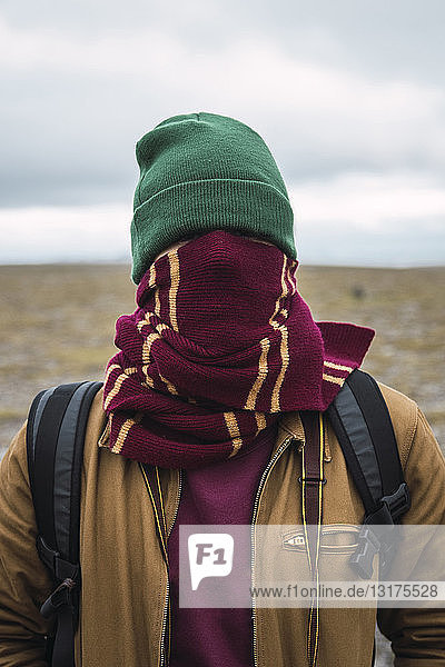 Young man with woolly hat and scarf  wrapped around face