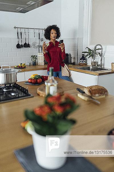 Woman drinking white wine in her kitchen  using smartphone