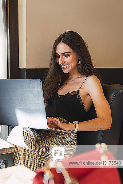 Portrait of smiling young woman in a coffee shop using laptop