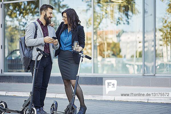 Lächelnder Geschäftsmann und Geschäftsfrau mit Rollern im Gespräch auf dem Bürgersteig