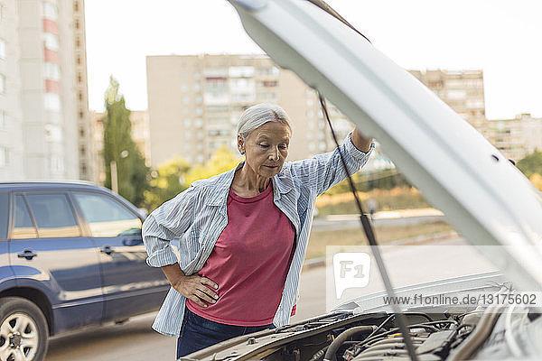 Ältere Frau betrachtet Automotor