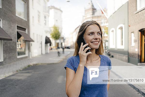 Niederlande  Maastricht  lächelnde junge Frau am Handy in der Stadt