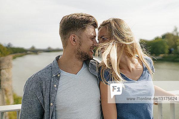 Liebenswertes junges Paar auf einer Brücke über einem Fluss