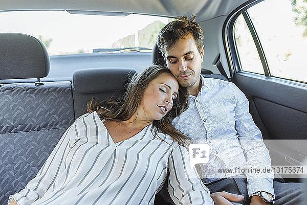Frau schläft auf dem Rücksitz eines Autos und lehnt sich an den Mann
