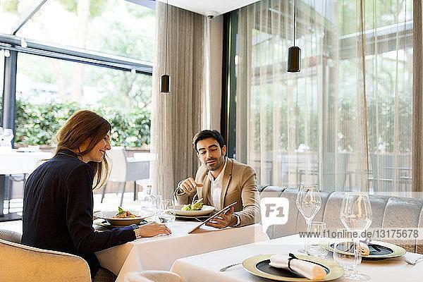 Mann und Frau teilen sich eine Tablette in einem Restaurant