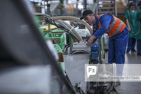 Mann arbeitet in der Fabrik an der Maschine