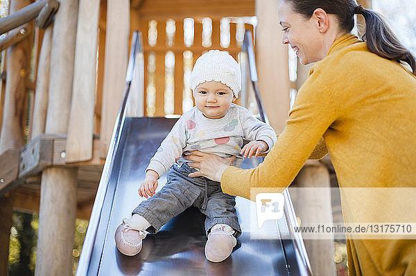 Porträt eines kleinen Mädchens  das auf einer Rutsche auf dem Spielplatz sitzt und von seiner Mutter gehalten wird
