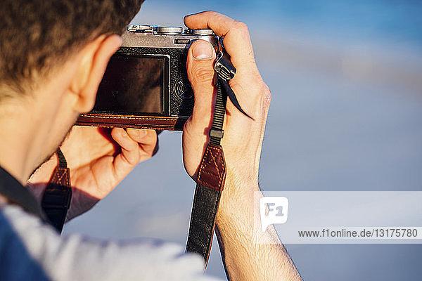 Nahaufnahme eines jungen Mannes  der mit einer altmodischen Kamera fotografiert
