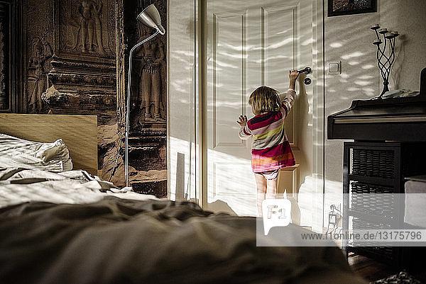 Rückansicht eines kleinen Mädchens  das zu Hause die Schlafzimmertür öffnet
