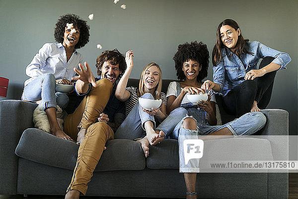 Überschwängliche Freunde sitzen auf der Couch und werfen Popcorn