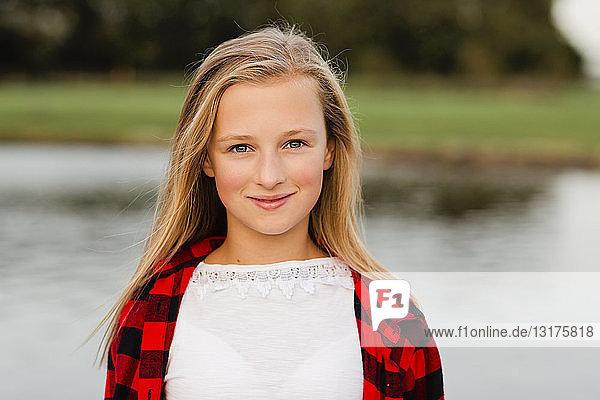 Porträt eines lächelnden blonden Mädchens in Natur